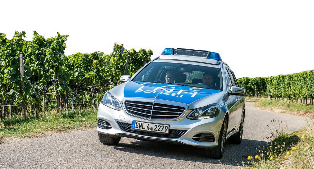 Ein Polizeiauto fährt auf einem Wirtschaftsweg in einem Weinberg.