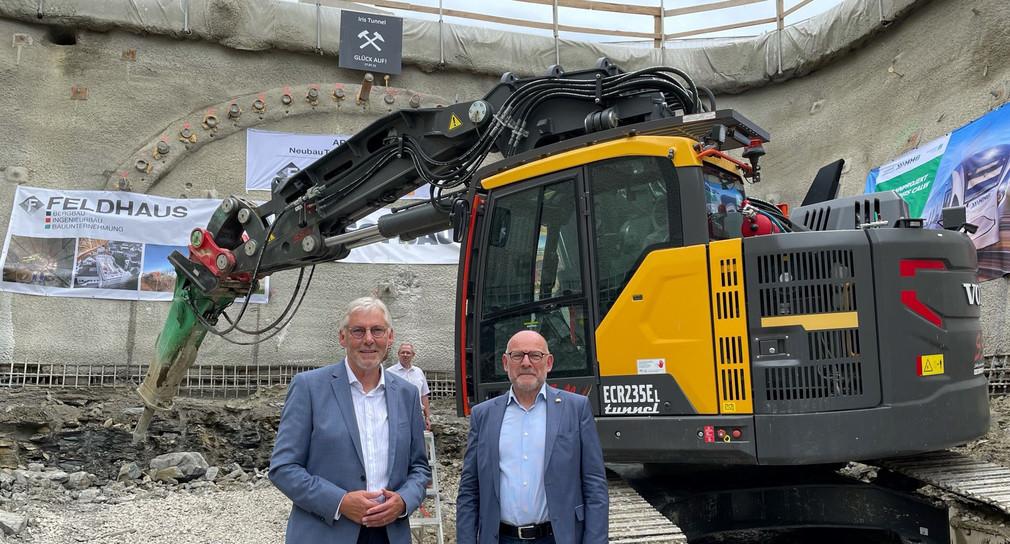 Landrat Helmut Riegger und Verkehrsminister Winfried Hermann stehen vor einem großen Bagger. Im Hintergrund sieht man den eingezeichneten Tunnel der Hermann-Hesse-Bahn.