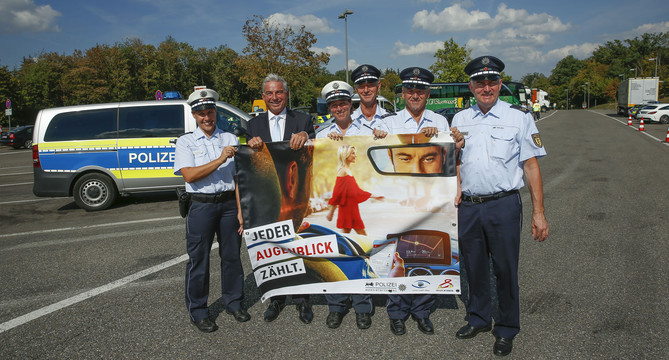 """Innenminister Thomas Strobl und Polizistinnen und Polizisten mit einem Plakat zur Verkehrsssicherheitsaktion """"sicher.mobil.leben"""" (Foto: © Innenministerium Baden-Württemberg)"""