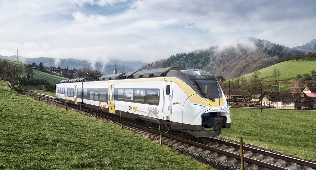 Ein weiß gelber Zug fährt auf Schienen durch eine grüne Landschaft.