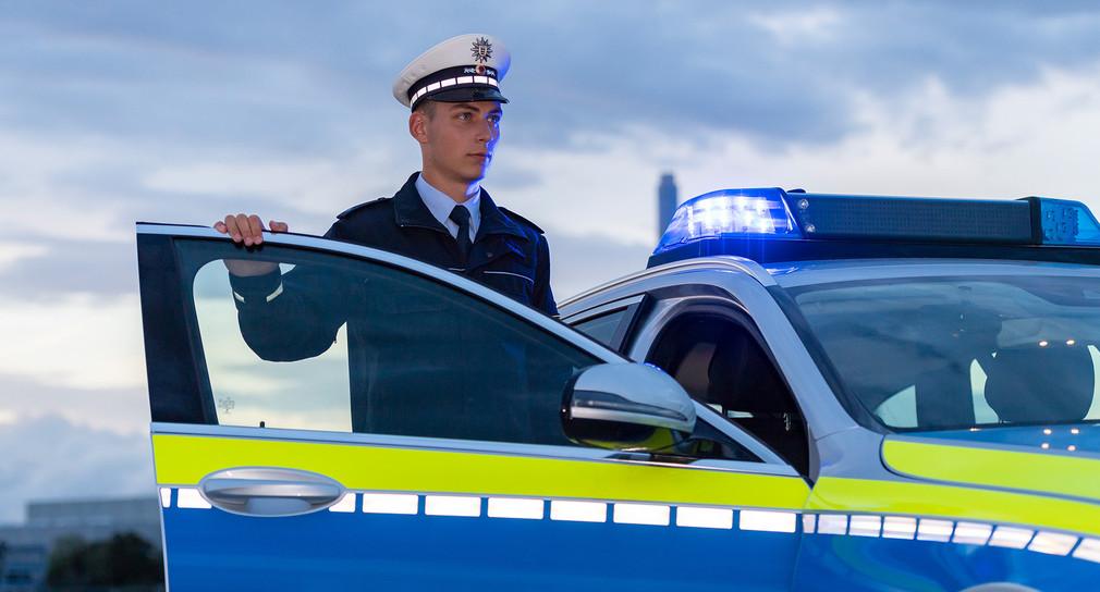 Junger Polizeibeamter vor einem Streifenwagen.