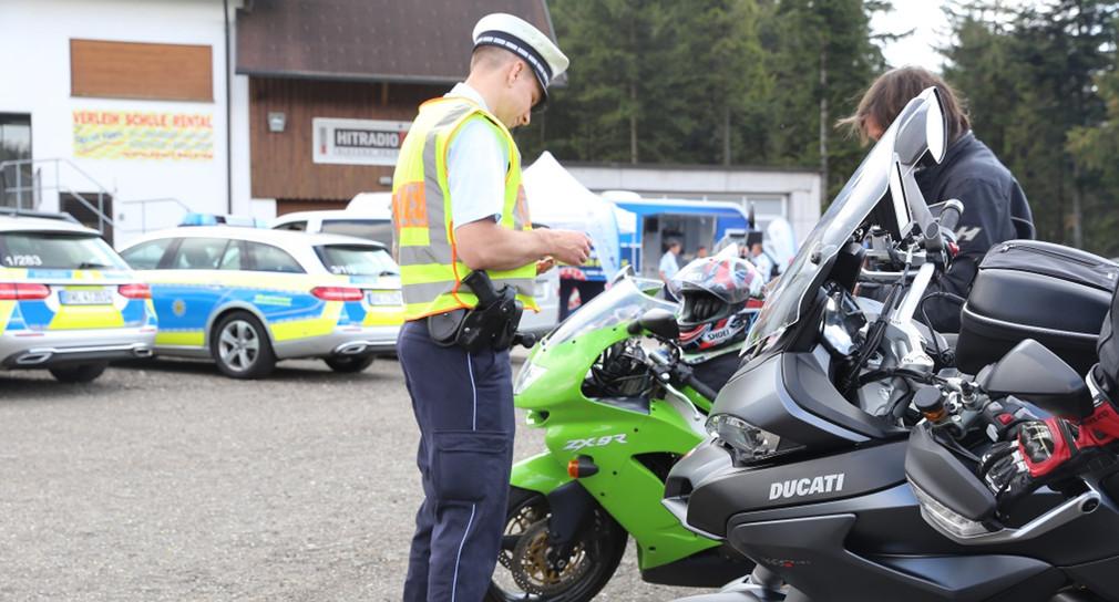 Ein Polizeibeamter kontrolliert einen Motorradfahrer.